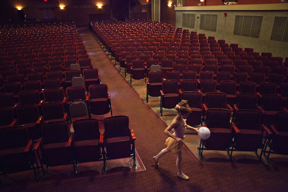 Caroline White, 8, plays in the empty seats of the Center for the Arts in Concord, New Hampshire between performances of the 12 Days of Christmas. (Concord Monitor)