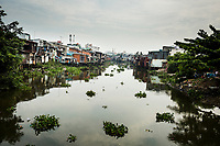 A small canal with houses built onto the water in Ho Chi Minh City, Vietnam.
