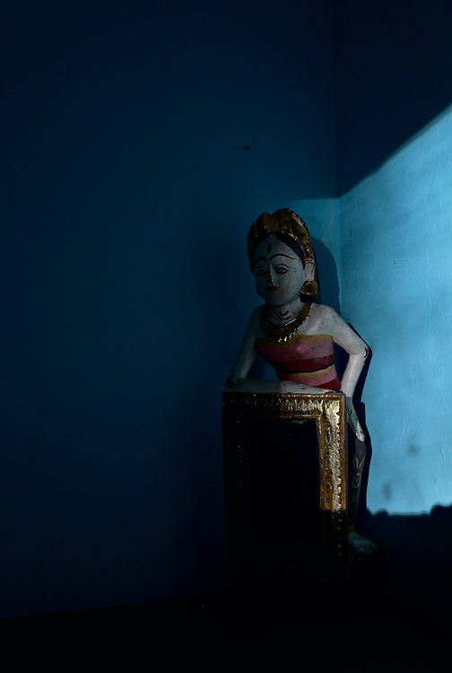 Colorful figurine mirror in shaft of sunlight against blue wall