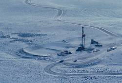 Stock aerial photograph of an on-shore workover drilling rig on a snow covered work site in Wyoming