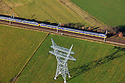 Nederland, Gelderland, Hattem, 20-01-2011; Hoogspanningsmast in een weiland, omgeving Hattemerbroek met passerende  Intercity Zwolle-Amersfoort .Power pylonin a meadow near the village of Hattemerbroek, train passing by..luchtfoto (toeslag), aerial photo (additional fee required).copyright foto/photo Siebe Swart