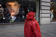 Dyed red hair woman and a large image of a male model in the window of clothing retailer H&M on Regents Street, London borough of Westminster.