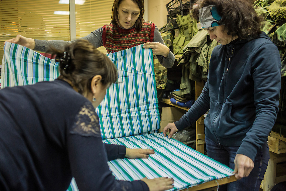 DNIPROPETROVSK, UKRAINE - NOVEMBER 16, 2014:  Tanya Volynets, 46, a lawyer, Yana Sobolenko, 39, an engineer, and Lyudmyla Makaida, 48, a designer, from left, prepare fabric they will use to sew underwear for soldiers at the Dnipropetrovsk Volunteer Logistics Center, a charity organization that produces supplies for pro-Ukrainian fighters battling rebels in the country's East, in Dnipropetrovsk, Ukraine. CREDIT: Brendan Hoffman for The New York Times
