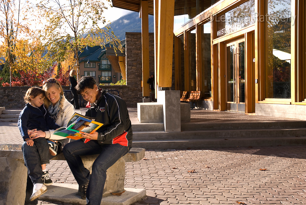 A family walks out of the Whistler Public Library after checking out some books on a sunny autumn day in Whistler, BC Canada