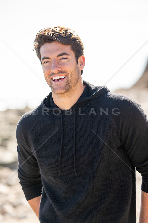 good looking man smiling outdoors on the beach