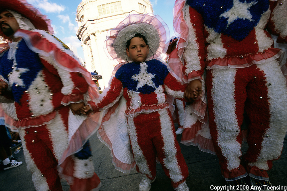 PUERTO RICO - APRIL 10: A family parades in Puerto Rican flag costumes at the annual Carnival celebration on April 10, 2002 in Ponce, Puerto Rico. Puerto Rico was an outpost of Spanish colonialism for 400 years, until the United States took possession in 1898. Today Puerto Rico's Spanish-speaking culture reflects its history - a mix of African slaves, Spanish settlers, and Taino Indians. Puerto Ricans fight in the U.S. armed forces but are not entitled to vote in presidential elections. They passionately debate their relationship with the U.S. with about half the island wanting to become the 51st state and the other half wanting to remain a U.S. commonwealth. A small percentage feel the island should be an independent country. While locals grapple with the evils of a burgeoning drug trade and unchecked development, drumbeats still drive the rhythms of African-inspired bomba music. (Photo By Amy Toensing) _________________________________<br />