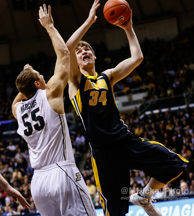 WEST LAFAYETTE, IN - JANUARY 27: Adam Woodbury #34 of the Iowa Hawkeyes shoots over Sandi Marcius #55 of the Purdue Boilermakers at Mackey Arena on January 27, 2013 in West Lafayette, Indiana. Purdue defeated Iowa 65-62 in overtime. (Photo by Michael Hickey/Getty Images) *** Local Caption *** Adam Woodbury; Sandi Marcius