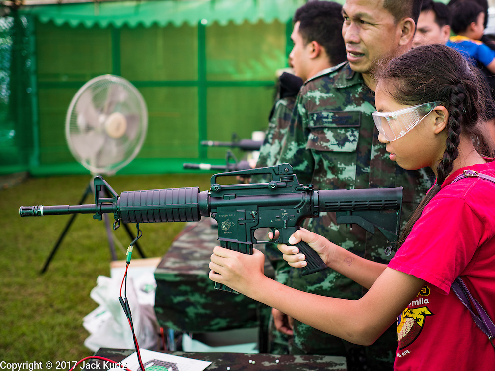 """14 JANUARY 2017 - BANGKOK, THAILAND: Thai children shoot bb guns modeled on the M16 assault rifle during Children's Day activities at the King's Guard, 2nd Cavalry Division base in Bangkok. Thailand National Children's Day is celebrated on the second Saturday in January. Known as """"Wan Dek"""" in Thailand, Children's Day is celebrated to give children the opportunity to have fun and to create awareness about their significant role towards the development of the country. Many government offices open to tours and military bases hold special children's day events. It was established as a holiday in 1955.        PHOTO BY JACK KURTZ"""