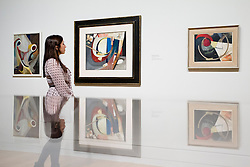 © Licensed to London News Pictures. 28/01/2013. London, UK. A Tate Britain employee views 'Untitled (Picture with Wooden Ring)' (1941) an oil painting by Kurt Scwitters at the press view of an exhibition of the artists work taking place at the Tate Britain in London. The exhibition, 'Schwitters in Britain', is the first to to examine the work of the late German modernist artist's 'British period' (1940-1948), and runs from 30th of January 2013 to the 12th of May 2013. Photo credit: Matt Cetti-Roberts/LNP