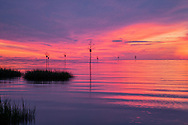 A colorful post-sunset sky reflects in Cape Cod Bay at Rock Harbor