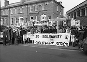 Anti Apartheid Protest.    (N69)..1981..08.04.1981..04.08.1981..8th April 1981..In protest against a forthcoming Irish rugby tour to South Africa, members of the anti-apartheid movement held a protest at Irish Rugby headquarters. The group made up of both religious and laity were trying to encourage the rugby authorities to cancel the tour which they saw as giving credibility to a corrupt system of government...Image shows the protest group forming at Lansdowne Road,Dublin. Posters were prominent in outlining the inequality of the black population in South Africa.