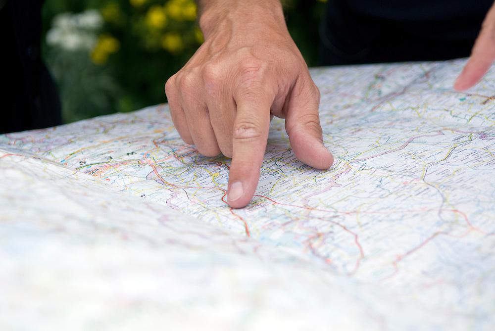 Der  Zeigefinger einer rechten  Hand eines Mannes zeigt auf eine Strassenkarte - street map index finger