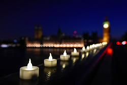 © Licensed to London News Pictures. 24/03/2017. London, UK. Electric candles have been laid out at the south end of Westminster Bridge in tribute to the victims of the terrorist attack in Westminster where five lost their lives and 40 people were injured. Photo credit : Stephen Chung/LNP