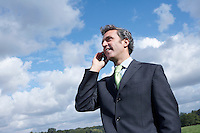 Business man talking on mobile phone in meadow