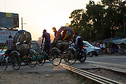 Cars and rickshaws crossing the railway line as the sun sets in Dhaka, Bangladesh.
