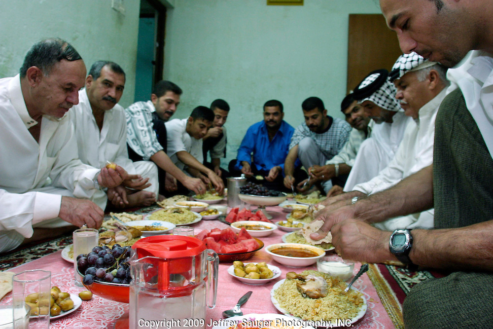 Malik Al-kasid, left, and his son Emad Al-kasid, right, eat their first meal with extended family members at home of Malik's sister Batuol Al-kasid. The Al-kasid family fled Iraq after the Gulf War and their part in the uprising against Saddam Hussein in 1991, spent 3 years in Rafa, Saudi Arabia and finally settled in Dearborn, MI. The family hasn't been home to Iraq in 13 years.