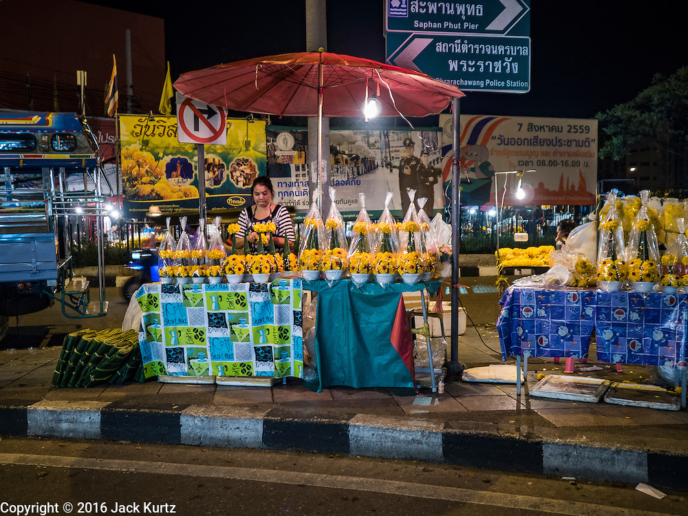 30 JUNE 2016 - BANGKOK, THAILAND:  A vendor selling marigolds on a sidewalk near Pak Khlong Talat. Sidewalk vendors around Pak Khlong Talat, Bangkok's famous flower market, face eviction if they reopen July 1. As a part of the military government sponsored initiative to clean up Bangkok, city officials have been trying to shut down the sidewalk vendors around the flower market. The vendors were supposed to be gone by the end of March, but city officials relented at the last minute with a compromise allowing vendors to stay until June 30. When vendors dismantled their booths after business on June 30, they weren't sure if they will be allowed to reopen July 1. Some vendors have moved to new locations approved by the government but many have not because they can't afford the higher rents in the new locations.    PHOTO BY JACK KURTZ