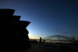 Silhouette of the Sydney Opera House at sunset with Sydney Harbor Bridge in the background, Sydney, New South Wales, Australia