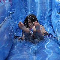 Madeline Randolph, 9, slides down one of four inflatable slides at the Tupelo Aquatic Center's Itty Bitty Beach Party Saturday