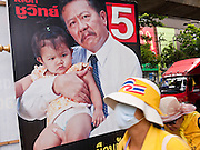 "22 JUNE 2011 - BANGKOK, THAILAND: Thai Yellow Shirts, who are calling for a ""no"" vote in the election, walk past a campaign poster in Bangkok, Thailand. Yingluck Shinawatra, leader of the Pheua Thai party is running against  incumbent Prime Minister Abhisit Vejjajiva, head of the Democrat party. Yingluck is the youngest sister of exiled former Prime Minister Thaksin Shinawatra, deposed by a military coup in 2006. Yingluck is currently leading in opinion polls, running well ahead of the Democrat party, which in one form or another has ruled Thailand for most of the last 60 years.   Photo by Jack Kurtz"