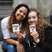 Tourists taken photo with a polaroid camera at St. Paul's Cathedral, on 18 July 2019, City of London, UK.