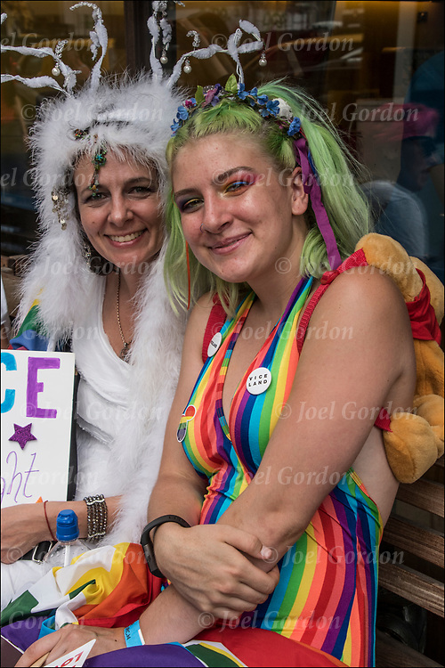 Portrait  from the 2018 Pride Parade,  two lesbians in the crowd watching the parade.<br /> <br /> This year's theme, &quot;Defiantly Different,&quot; was meant to be an &quot;unflinching stance&quot; in response to the Trump administration's treatment of the LGBTQ+ community<br /> <br /> The first March was held in 1970 and has since become an annual civil rights demonstration. Over the years, its purpose has broadened to include recognition of the fight against AIDS and to remember those we have lost to illness, violence and neglect.<br /> <br />  To prepare for historic attendance and participation expected for WorldPride and the 50th Anniversary of the Stonewall Uprising in 2019, NYC Pride will be changing the route for the NYC Pride March in 2018.
