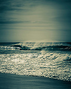 Early morning surf at Dudley Beach, NSW, Australia. Backlit small waves with off shore wind
