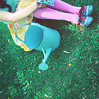 Close-up faceless photo of a young girl sitting in the grass, in summer clothes enjoying the sunshine, with a retro feel
