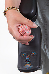 Hand resting on the joystick of a motorised wheelchair,