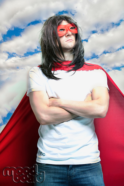 Young man in super hero costume with arms crossed against cloudy sky