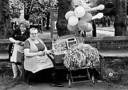 May Day &ndash; 1981 Knutsford<br /> These two flag sellers grabbed my attention as they reminded me of Les Dawson&rsquo;s Cissie &amp; Ada characters.  They were set up outside Knutsford&rsquo;s parish church with bundles of flags and balloons in their battered suitcase on an old pram stand.  The flags commemorated the forthcoming marriage of Prince Charles and Lady Diana Spencer.