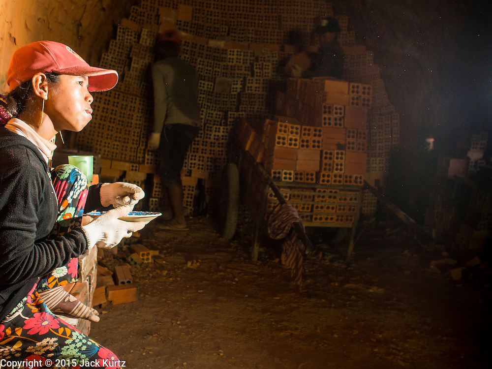 26 FEBRUARY 2015 - PHNOM PENH, CAMBODIA: A worker eats her lunch while her coworkers stack bricks on a handcart in a kiln at a brick making factory on the outskirts of Phnom Penh.    PHOTO BY JACK KURTZ
