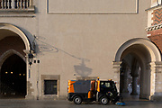A local authority street sweeper has paused during morning cleaning patrols beneath the architecture of the Cloth Hall and the the City Hall Tower (right) on Rynek Glowny market square, on 23rd September 2019, in Krakow, Malopolska, Poland.