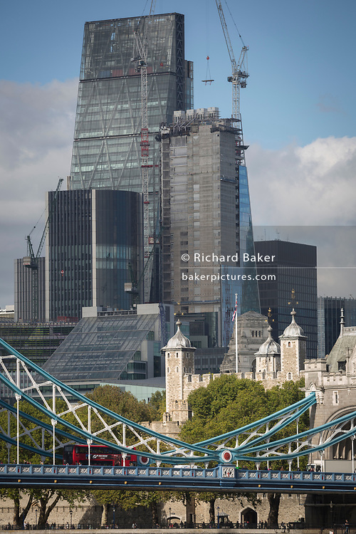 A red London bus crosses Tower Bridge with the Norman Tower of London and construction work in progress in the capital's financial district (aka The Square Mile) behind, on 5th October, 2017, in London, England.