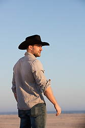 cowboy outdoors in a denim shirt against a blue sky