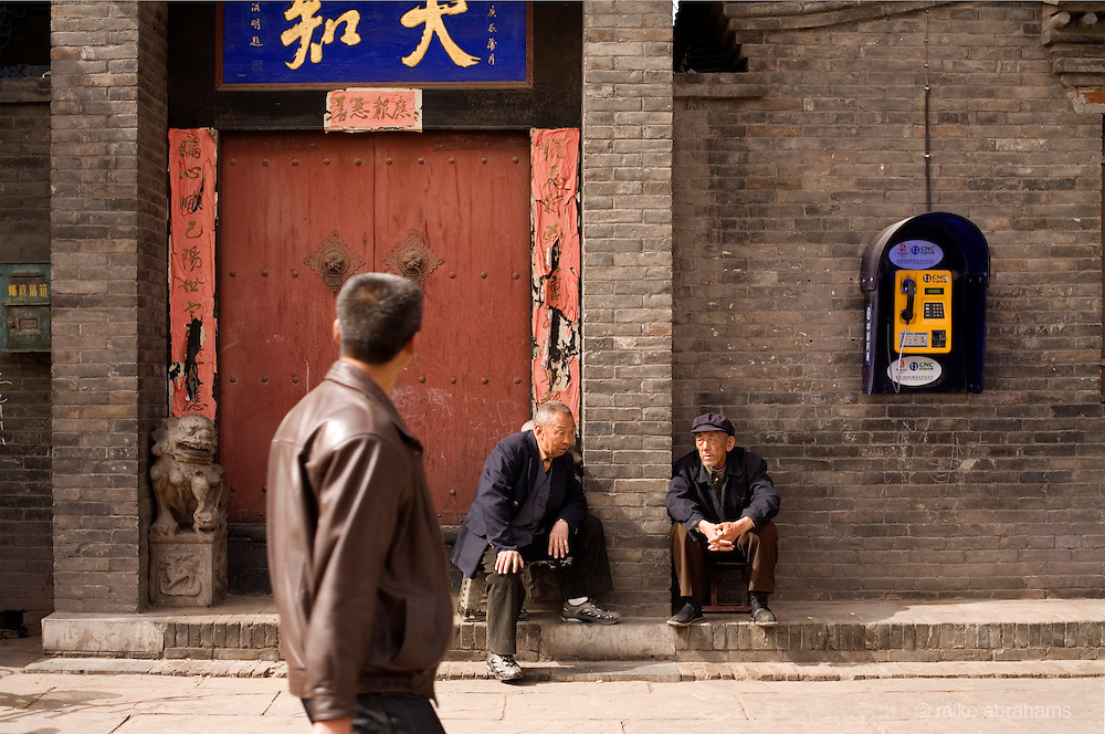 Two elderly men sit outside a doorway. Pingyao, People's Republic of China