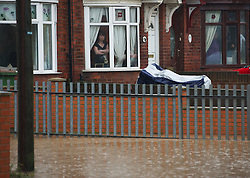 © Licensed to London News Pictures. 26/11/2012..Carlin How, England..A woman looks on as a huge part of the main road through Carlin How in East Cleveland was flooded after another night of heavy rain that caused disruption in parts of East Cleveland and North Yorkshire...Photo credit : Ian Forsyth/LNP