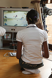 Black teenage girl playing wii game