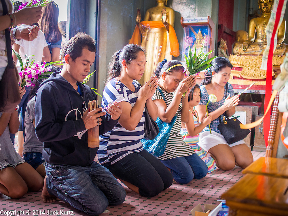 11 JULY 2014 - BANGKOK, THAILAND: Thais pray in a chapel at Wat Mahabut for Asalha Puja Day. Asalha Puja is the day the Lord Buddha preached his first sermon to followers after attaining enlightenment. The day is usually celebrated by merit making and listening to a monks' sermons. It is also day before the start of the Rains Retreat, the three month period when monks stay in their temple for intense mediation and spiritual renewal.   PHOTO BY JACK KURTZ