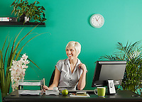 Business woman behind desk in office full of potted plants