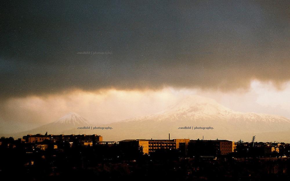 Dunkle Gewitterwolken ziehen im Frühsommer über die armenische Hauptstadt Eriwan. Am Horizont die schneebedeckten Hänge des 5165 Meter hohen Ararats.  A thunderstorm above Yerevan, Armenia.