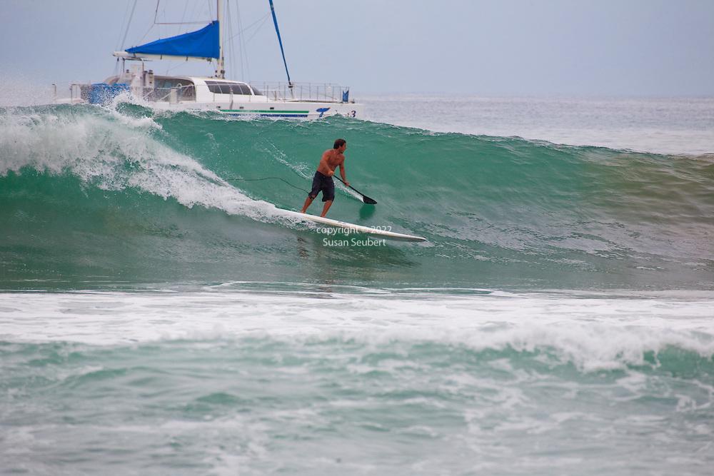 Paddleboard surfing in head high waves at Ka'anapali Point on Maui, HI