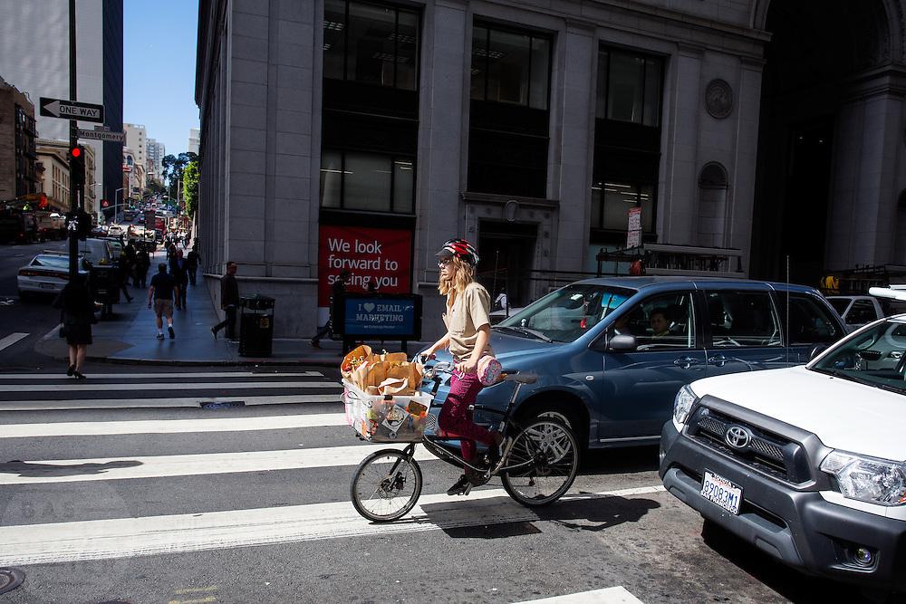 Fietsers rijden in de Financial District in San Francisco waar veel hoofdkantoren van banken en grote ondernemingen zijn gevestigd. De Amerikaanse stad San Francisco aan de westkust is een van de grootste steden in Amerika en kenmerkt zich door de steile heuvels in de stad.<br /> <br /> Cyclists at the Financial District of San Francisco where headquarters of banks and financial companies are located. The US city of San Francisco on the west coast is one of the largest cities in America and is characterized by the steep hills in the city.