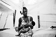 Haiti Earthquake, Port au Prince.<br /> Woman breast feeding her child inside a shelter with mosquito net.