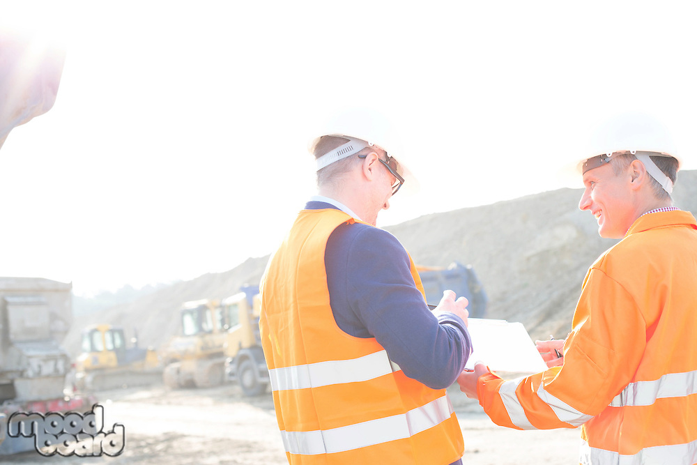 Happy engineers discussing over clipboard at construction site against clear sky