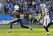 Dec 31, 2017; Carson, CA, USA; Los Angeles Chargers wide receiver Travis Benjamin (12) is pursued by Oakland Raiders strong safety Shalom Luani (26) on a 62-yard touchdown reception in nteh third quarter during an NFL football game at StubHub Center. The Chargers defeated the Raiders 30-10.