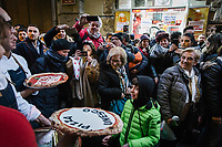 "NAPLES, ITALY - 8 DECEMBER 2017: Pedestrians stop and photograph Gino Sorbillo, a Master Pizzaiuolo (pizza chef) and owner of Pizzeria Gino Sorbillo,  together with his brother Toto (right) and a pizzaiuolo (left) as hey hold commemorative pizzas to celebrate the art of Pizzaiuolo added to Unesco's list of Intangible Cultural Heritage of Humanity, here by his pizzeria in Naples, Italy, on December 8th 2017.<br /> <br /> On Thursday December 7th 2017, UNESCO added the art of Neapolitan ""Pizzaiuolo"" to its list of Intangible Cultural Heritage of Humanity.<br /> <br /> The art of the Neapolitan 'Pizzaiuolo' is a culinary practice comprising four different phases relating to the preparation of the dough and its baking in a wood-fired oven, involving a rotatory movement by the baker. The element originates in Naples, the capital of the Campania Region, where about 3,000 Pizzaiuoli now live and perform. Pizzaiuoli are a living link for the communities concerned. There are three primary categories of bearers – the Master Pizzaiuolo, the Pizzaiuolo and the baker – as well as the families in Naples who reproduce the art in their own homes. The element fosters social gatherings and intergenerational exchange, and assumes a character of the spectacular, with the Pizzaiuolo at the centre of their 'bottega' sharing their art.<br /> <br /> In Naples, pizza makers celebrated the victory by giving away free pizzas."