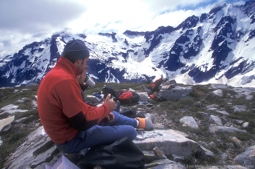 Forrest Murphy and Marshall Balick enjoy a cup of early morning coffee on Challenger Arm in the North Pickets, North Cascades National Park. Behind them is Luna Peak, snow covered Luna Lake and Mt. Fury.