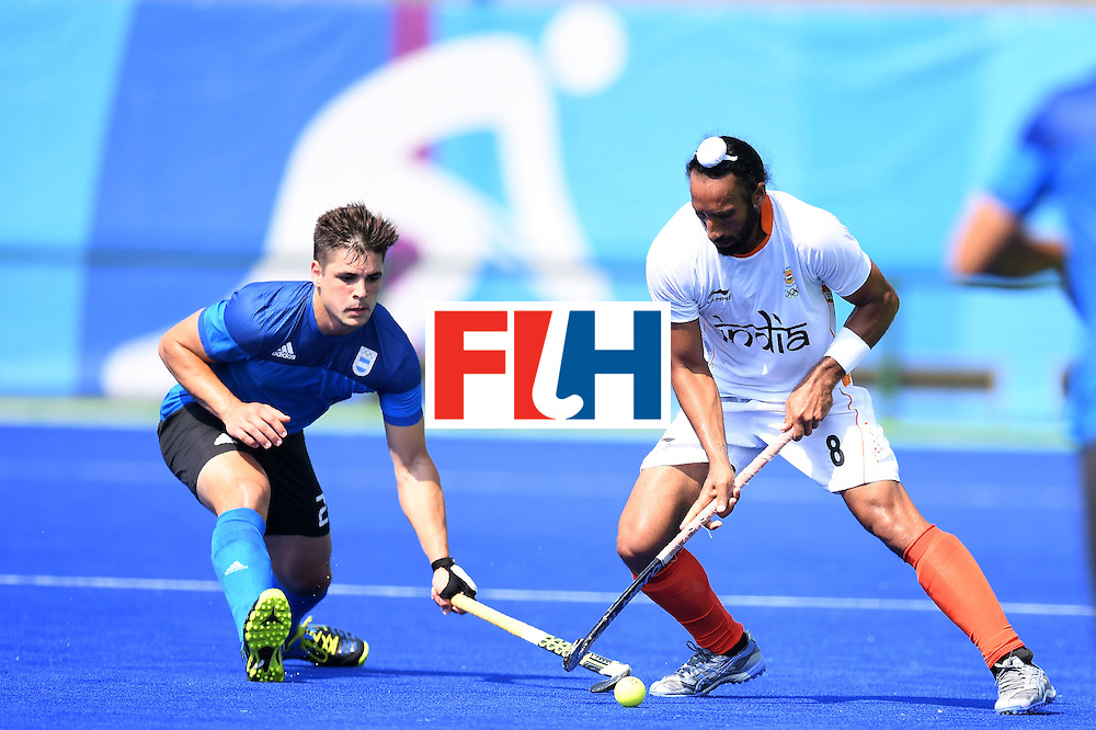 India's Sardar Singh (R) vies for the ball with Argentina's Gonzalo Peillat during the men's field hockey Argentina vs India match of the Rio 2016 Olympics Games at the Olympic Hockey Centre in Rio de Janeiro on August, 9 2016. / AFP / MANAN VATSYAYANA        (Photo credit should read MANAN VATSYAYANA/AFP/Getty Images)