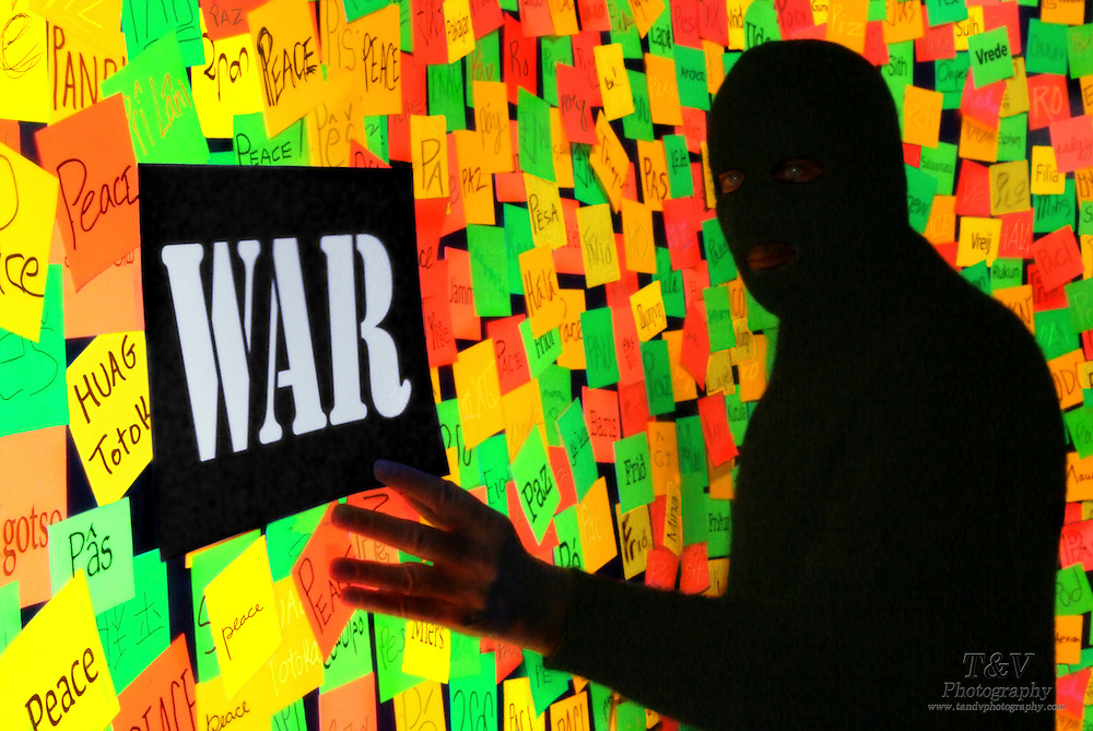 Terrorist places a war sign  on a wall posted with the word peace in numerous languages.Black light